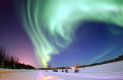 A blue-green-aurora swirling over a snowy landscape