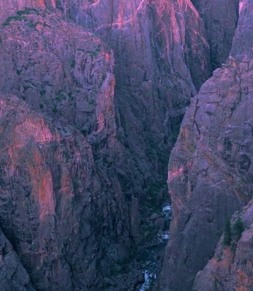 A deep canyon with nearly vertical sides, formed of dark rock with a magenta cast.