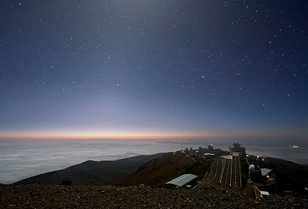 A dark blue starry sky. with light on the horizon, over a plain and an observatory.